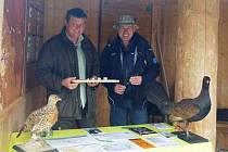 Pavel Veverka z NP Šumava (v kloboučku) a vedle něho Roland Ertl z NP Bavorský les v mobilní expozici o tetřevech.