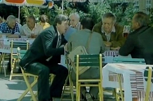 Záběr zfilmu Neříkej mi majore! Letní terasa se slunečníky a zahradními stolky vyrostla  před hotelem vTrhových Svinech kvůli filmu. Kromě herců (Miroslav Zounar vtmavém saku) na ní sedli imístní komparzisté.