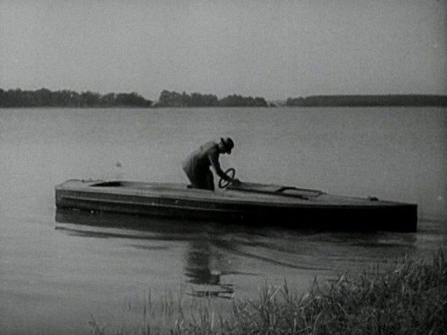 """Na hladině startuje neznámý muž jednoduchý dřevěný člun, který má zachránit oba """"plavce""""."""