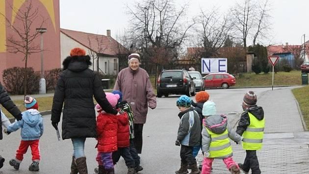 Před referendem se na plotě v centru Zlivi objevil velký plakát s nápisem NE (v pozadí).