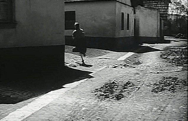 Dolejší ulice v Mirovicích. Dům vlevo, kolem něhož běží dívka, je zbouraný, vpravo stále stojí.