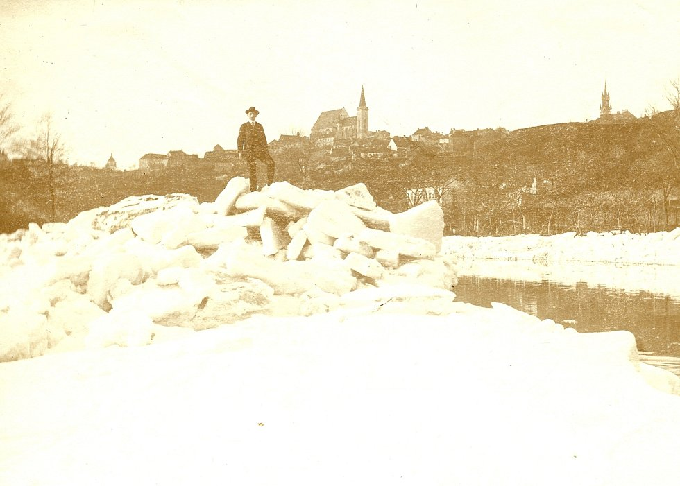 Muž v obleku stojící na hromadě ledu - ledová zácpa na Dyji, v pozadí město Znojmo s kostelem sv. Mikuláše, hradem apod. (kolem roku 1912). Autorem je Heinrich Homma.