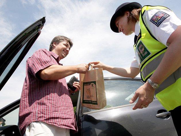Policistka předává slušnému řidiči pivo.