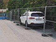 V brněnské Francouzské ulici dělníci obehnali dočasným plotem zaparkované auto.