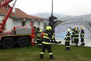 Kobyla spadla do díry u bazénu. Před utonutím ji zachránili hasiči a jeřáb