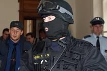 Zásahová jednotka vězeňské služby dohlíží na bezpečnost obžalovaných.