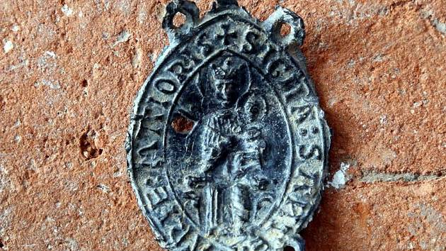 """Významný je nález poutního odznaku ze 13. století. """"Ve středověku se jimi označovali lidé, kteří se vydali na zbožnou cestu například do Říma. Okolí tak vědělo, co jsou zač a poutníky chránily,"""" vysvětlil  vedoucí archeologického týmu Antonín Zůbek."""