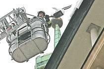 Brněnští hasiči sundávají sníh ze střech domů.