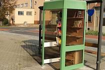 Lidé si půjčují knihy z knihobudky před ivančickým nádražím.