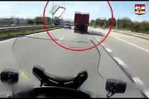 Velký kus kartonu letící z kamionu v pátek odpoledne těsně minul policistu jedoucího na motorce po dálnici D1.
