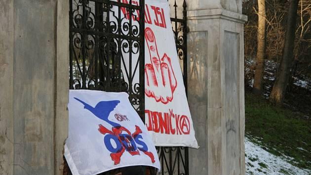 Transparenty proti Václavu Klausovi na bráně krumlovského zámeckého parku