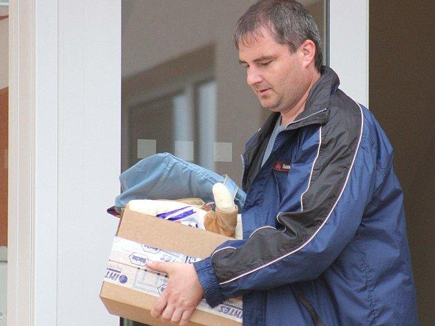 Kriminalista u Klokánku nese krabici s osobními věcmi dětí.