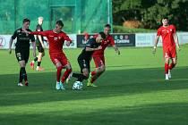 Fotbalista Dominik Havlín (v červeném s číslem 77) si v této sezoně zvyká na úroveň divize D.