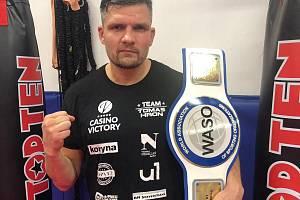 Thajboxer Tomáš Hron pózuje s pásem pro světového šampiona organizace WASO.