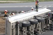 Naložený písek z havarovaného nákladního auta zablokoval dva pruhy.