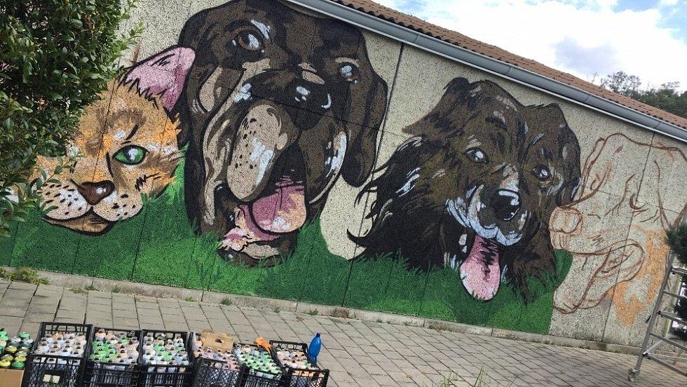 Venkovní stěnu u útulku zdobí malba tří psů a kočky.