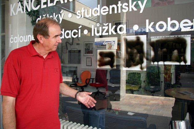 PROTI. Neznámý vandal začernil výlohu obchodu Františka Kocmana tam, kde visí petice řečkovických stárků.