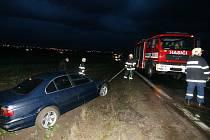 Hasiči vyprošťují auto v poli v městské části Slatina.