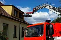 Záchranářům pomáhaly se snesením nadměrného pacienta dvě jednotky hasičů a speciální jeřáb.