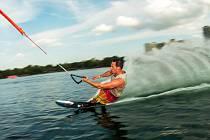 Nadšenci vodních sportů se po hladině projedou na prkně, které na laně potáhne vlek.