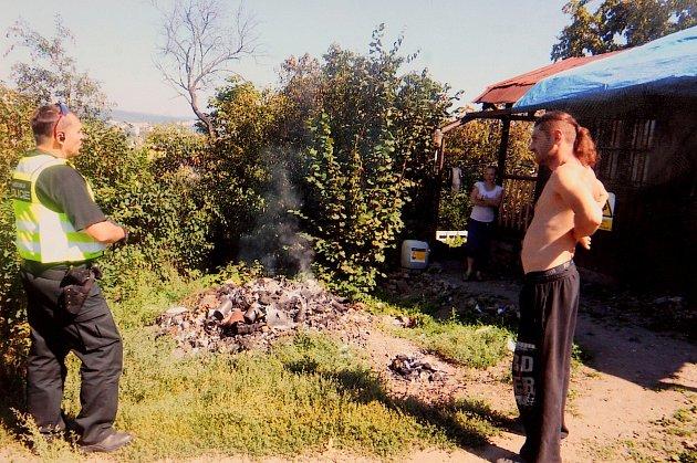 Hromada částečně spáleného odpadu vzahrádkářské kolonii Juranka. Věc řeší policista sdvěma bezdomovci. Nafoceno letos prvního září.