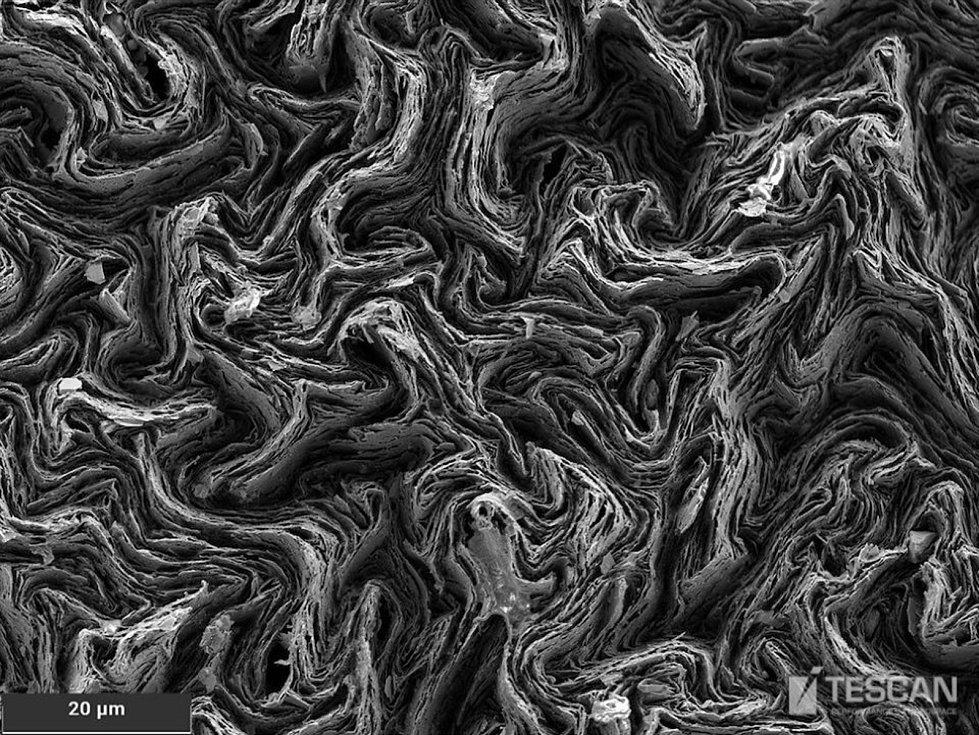 Tuha z mikrotužky s viditelnými vrstvami grafiku na snímku elektronového mikroskopu.
