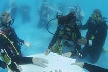 Svatba pod vodou - nevěsta Kateřina Šrajerová podepisuje a manžel Jiří Štancl ji přidržuje