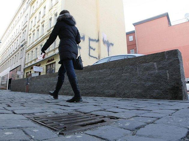 Parkoviště na brněnském Římském náměstí, kterému dominuje masivní zeď přímo uprostřed ústí Františkánské ulice.