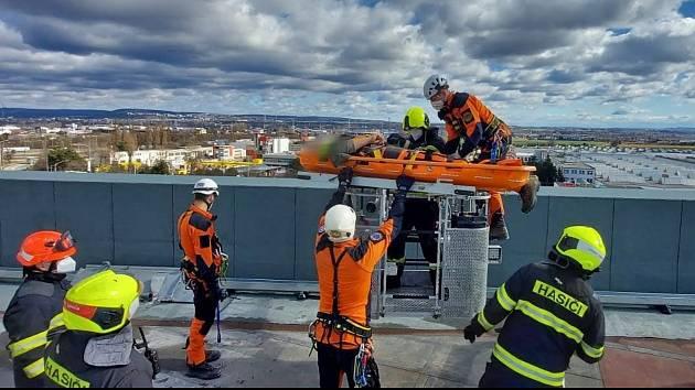 Hasiči pomáhali s transportem zraněného ze střechy obchodního domu.