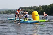 Při paddleboardingu projíždí závodníci trasu vytyčenou bójkami.