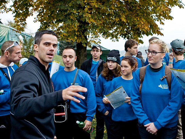 Ředitel Triexpert Vokolo príglu Petr Božek (v černém) udílí pokyny dobrovolníkům před startem závodu.