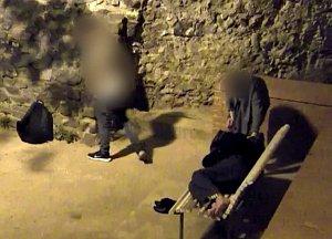 Mladící prohledávají tašku spícího muže