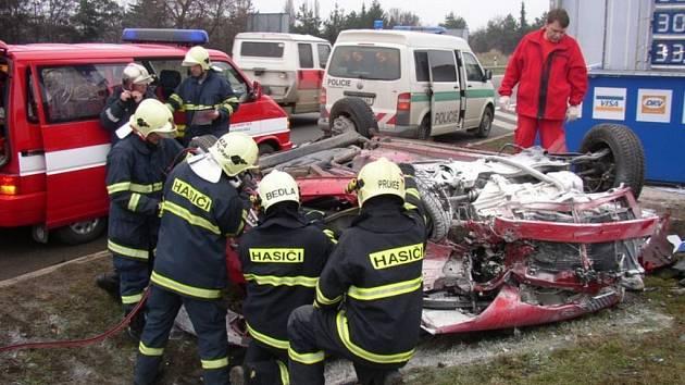 Hasiči likvidují vrak havarovaného auta