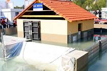 Povodně ve zmenšeném měřítku se odehrávají v bazénu, v němž je postavený model rodinného domu.