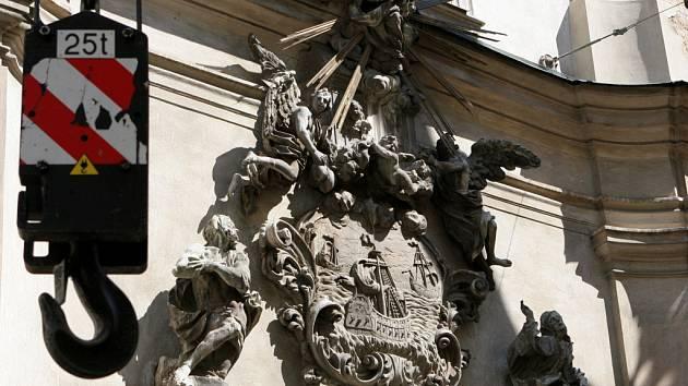Sundávání těžkých dekorací kostela svatých Janů.