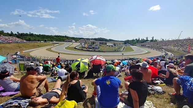 Fanoušci ze zaplněných tribun sledují závody motocyklové Velké ceny na brněnském Masarykově okruhu.
