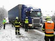 Sněžení přináší víc nehod a komplikací. Například na Blanensku ve stoupání silnice 43 u obce Závist mají problémy kamiony. Jednomu hasiči museli pomáhat (na snímku).