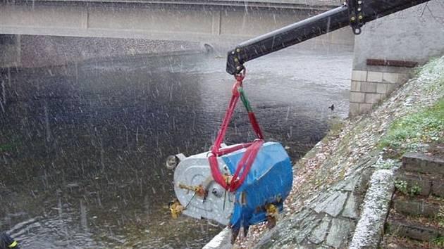Hasiči vytahují pomocí jeřábu kontejner z řeky