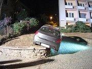 Při couvání k domu svým peugeotem uvízla řidička na vyvýšené zídce.