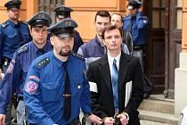 Policejní eskorta vede skupinu lupičů k soudu.