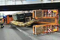 Převrácené nákladní auto blokující Hněvkovského ulici. Narazilo do mostní konstrukce.
