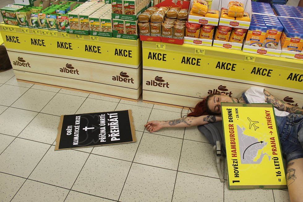 Aktivisté přestrojení za krávy a ovoce předstírali smrt v supermarketu, aby upozornili na klimatickou změnu.
