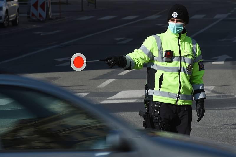 Brno 2.4.2020 - policista v roušce řídí dopravu v křižovatce ulic Veveří a Kotlářská