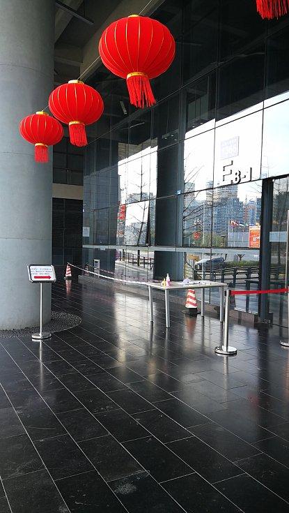 Kontrolní stanoviště před kancelářskou budovou v Chengdu. Při vstupu měří teplotu.