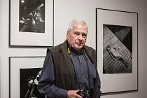 Brněnský fotograf Miloš Budík. V pozadí vlevo jsou jeho fotografie zachycující Gustava Broma a další hudebníky, kteří hrávali v klubu dnešní lékařské fakulty na Komenského náměstí.