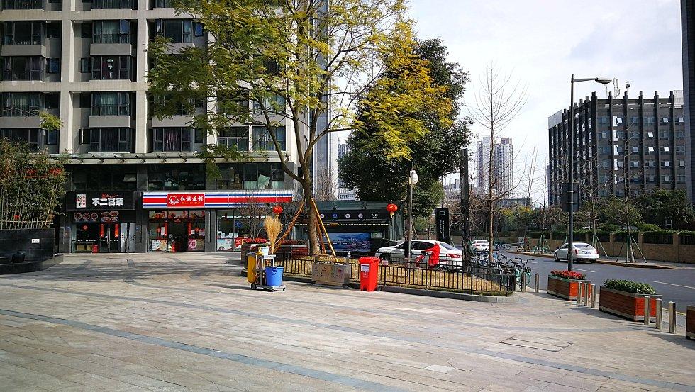 Vjezd do podzemních garáží v Chengdu. Červená popelnice je speciální na použité roušky.
