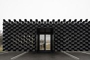 Galerie nábytku v brněnských Vinohradech. Prodejnu nábytku s fasádou z černých židlí navrhli architekti ze studia Chybik+Kristof Architects & Urban Designers.