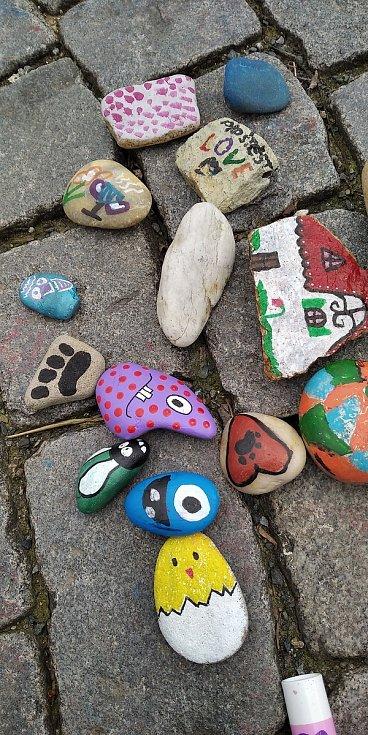 Lidé vkládají pomalované kamínky do srdce na Zelném trhu.