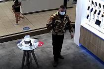 Muž je zachycen při nákupu v prodejně s mobilní elektronikou.