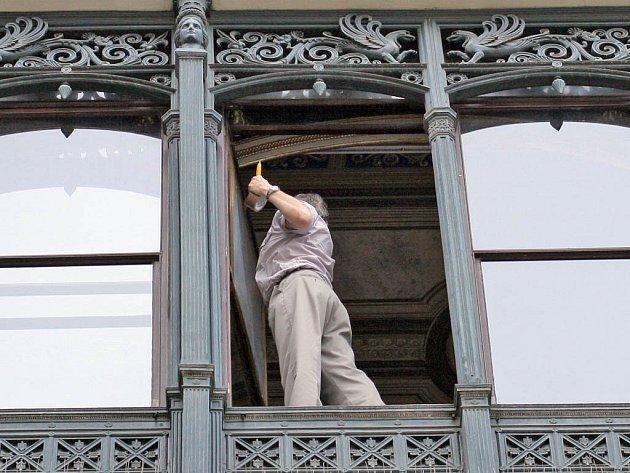 Pracovník zabezpečuje okno Kleinova paláce na náměstí Svobody.